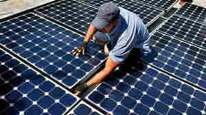 Damon Corkern installs solar panels on a roof
