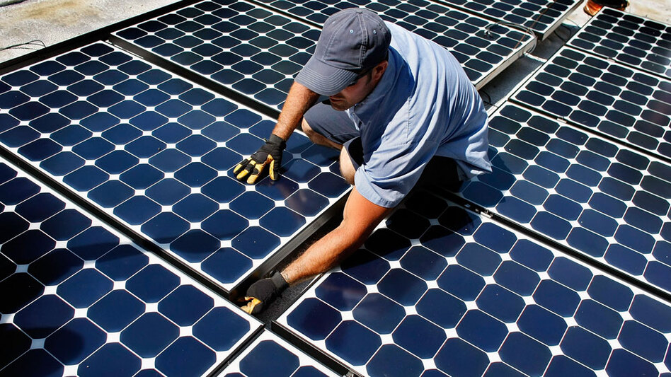 Damon Corkern, who works for ECS Solar Energy Systems, installs solar panels on a house roof in Gainesville, Fla.
