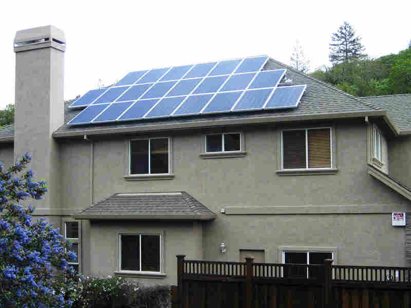 Solar panels sit atop a two-story home