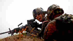 A soldier with Bravo Company, 101st Airborne Div., yells for more ammunition