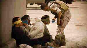 An Iraqi soldier gives water to detainees in Mosul, Iraq