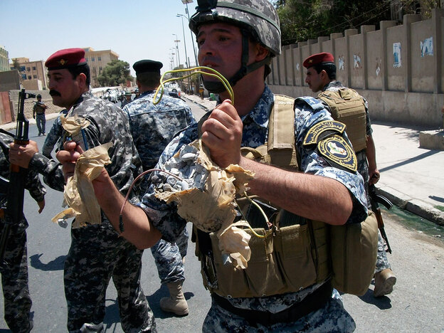 An Iraqi federal police officer holds an explosive device that was found in front of a hospital in Mosul and dismantled. It consisted of a water bottle filled with homemade explosives and rocks, with a cell phone initiator. It represents the kind of low-level attacks that continue in Mosul.