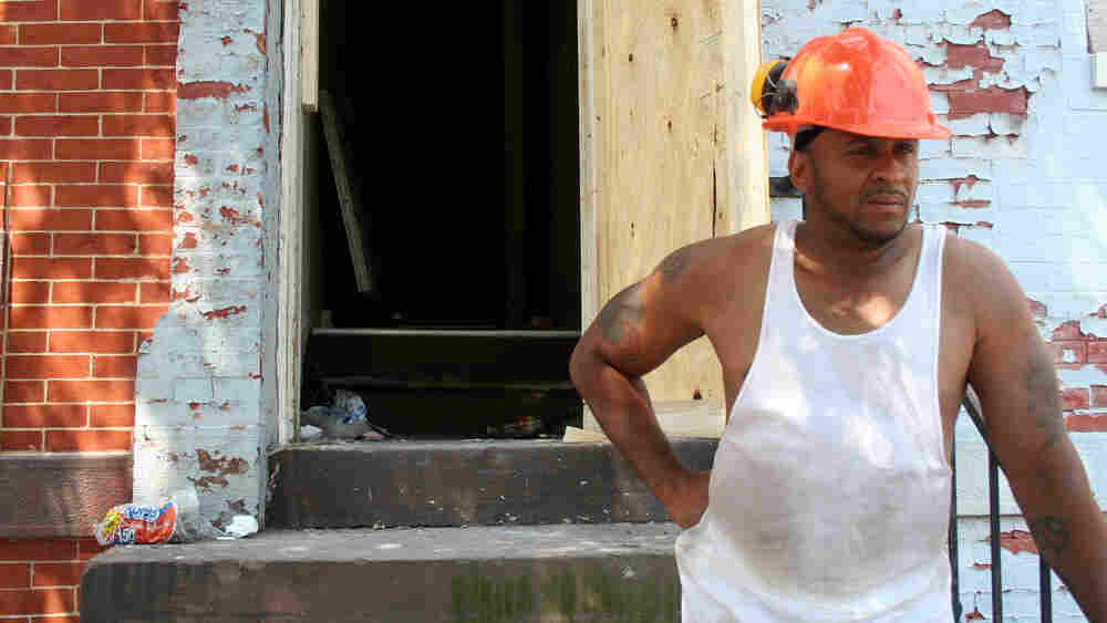 Neil Joseph outside a row house in Baltimore that he's rehabbing.