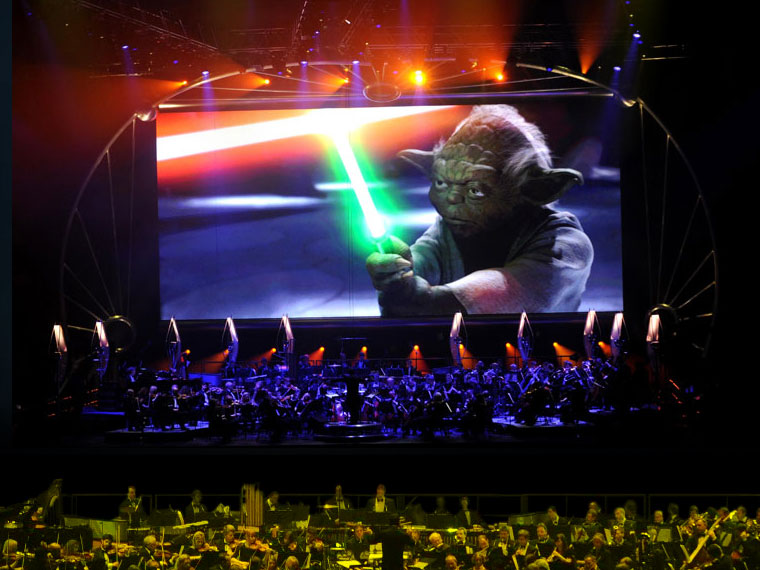 Yoda looks tough over the orchestra. StarWarsinconcert.com