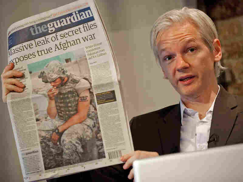WikiLeaks founder Julian Assange holds a copy of Monday's 'The Guardian' in London.