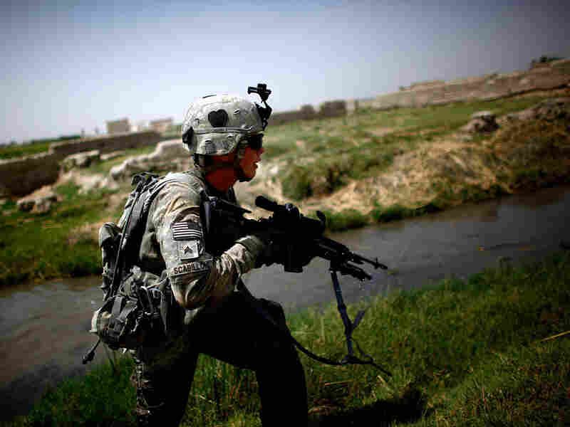 A U.S. soldier runs to take up position while coming under fire near an irrigation ditch in Pashmul,