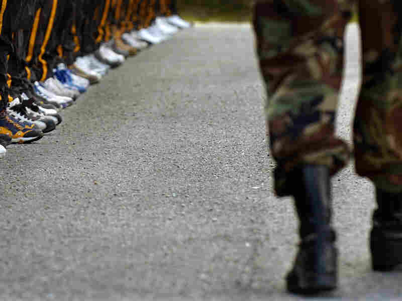 A drill sergeant passes a row of Army National Guard recruits.