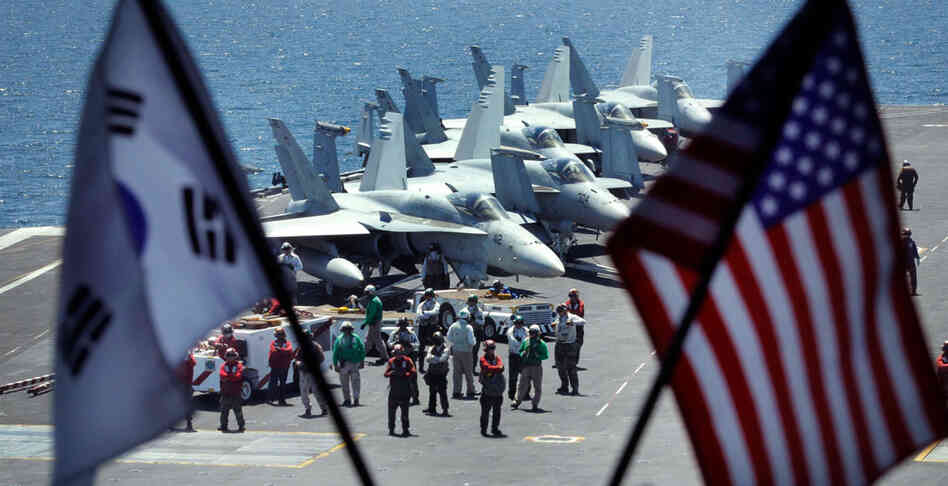 Crew members stand on the flight deck of the USS George Washington for joint military exercises.