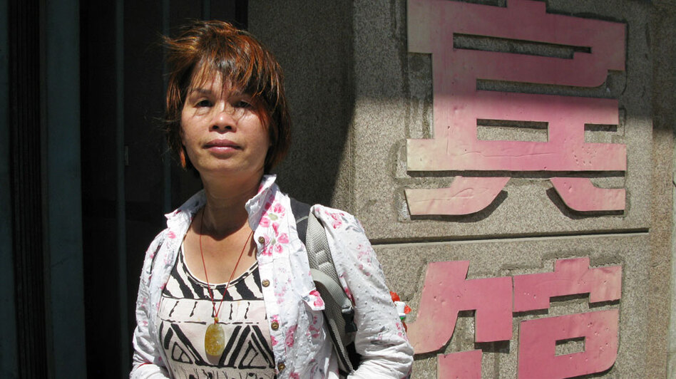 """Petitioner Liu Xinyu stands outside a Beijing hotel where she was recently detained by provincial officials. The hotel is run by the Guangxi provincial government's liaison office in Beijing. Unlike some secret detention facilities, known in China as """"black jails,"""" there are no iron bars on the hotel's doors or windows, but Liu says two female guards were hired to monitor her around the clock."""