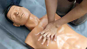 A woman performs chest compressions on a mannequin.