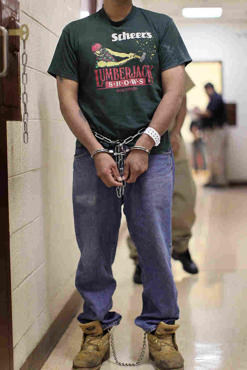An man wearing handcuffs waits to be deported