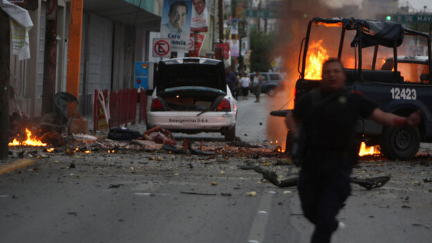 Police officer runs after attack on police trucks in Ciudad Juarez, Mexico, July 15.