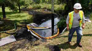 A worker monitors Talmadge Creek in Marshall Township, Mich.