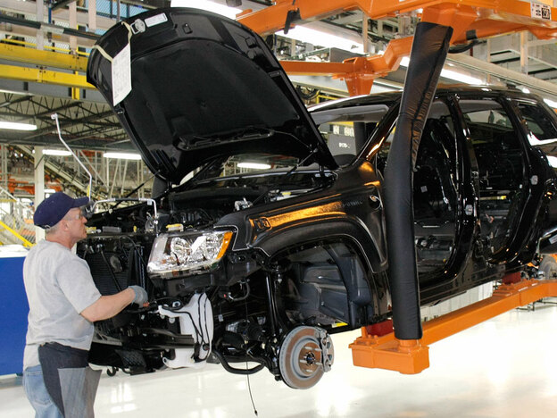 An employee works on the assembly line of the new Jeep Grand Cherokee at the Chrysler Jefferson Assembly plant in Detroit in May.