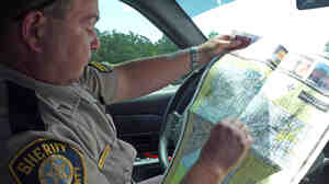 Cpl. Allen Harwood looks at a map in his patrol car. Gail Banzet/NPR