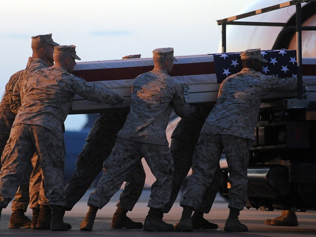 A Marine carry team lifts a transfer case containing the remains of Cpl. Paul J. Miller at Dover Air Force Base, Del., on July 21. Miller, of Traverse City, Mich., was killed by a roadside bomb blast while on patrol in Afghanistan. July was the deadliest month for U.S. troops in the nearly nine-year-old war.