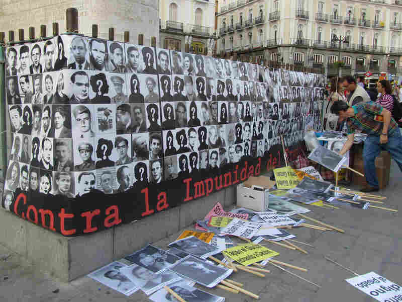 A banner displays photos of victims of Francoism who were executed or went missing.