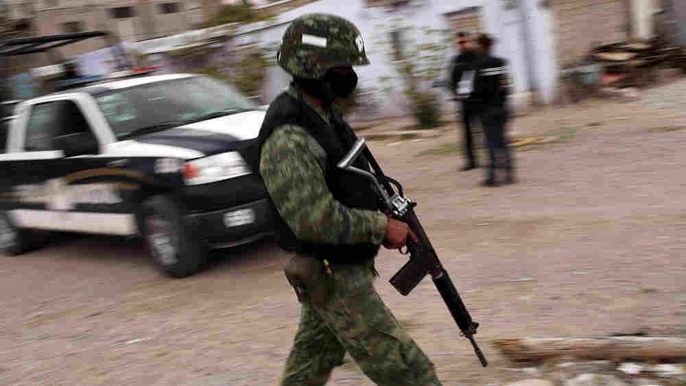 Military police stand guard at the scene of a murder in Juarez, Mexico in March.