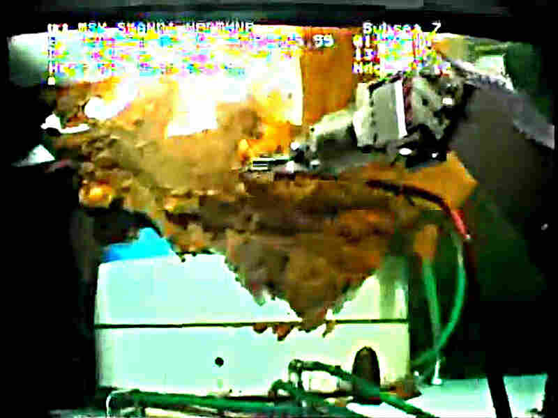 A robotic arm from a submersible works around the leaking wellhead in this video image.