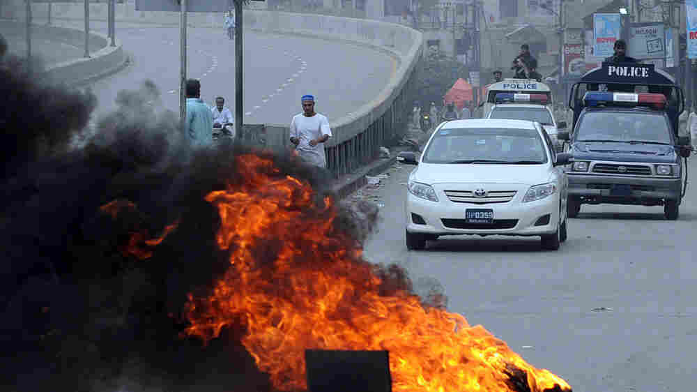 Pakistani policemen patrol on vehicles following overnight violence in Karachi.