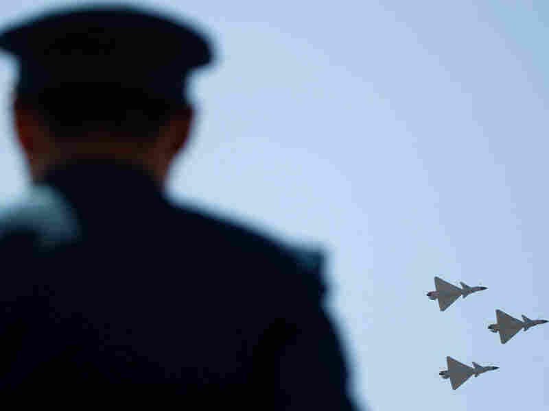 Chinese J-10 fighter jets fly-by in formation as an air force personnel stands guard