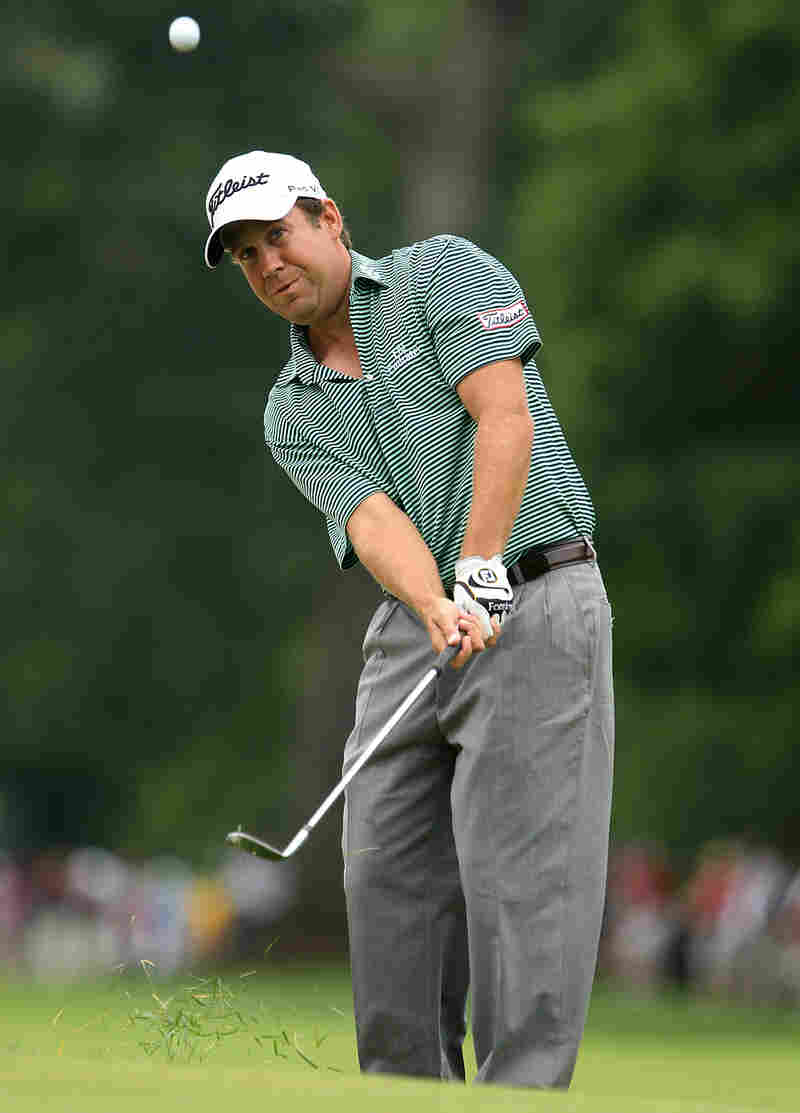 Erik Compton hits a pitch shot on the first hole during the final round of the Greenbrier Classic.