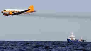 A dispersant plane passes over an oil skimmer in the Gulf of Mexico on April 27, 2010.