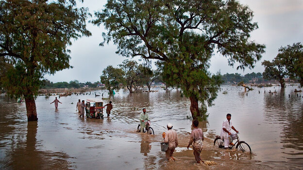 Local residents travel down a flooded road in the hard-hit district of Nowshera in Pakistan.