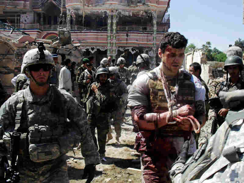U.S. soldiers escort a wounded foreign contractor