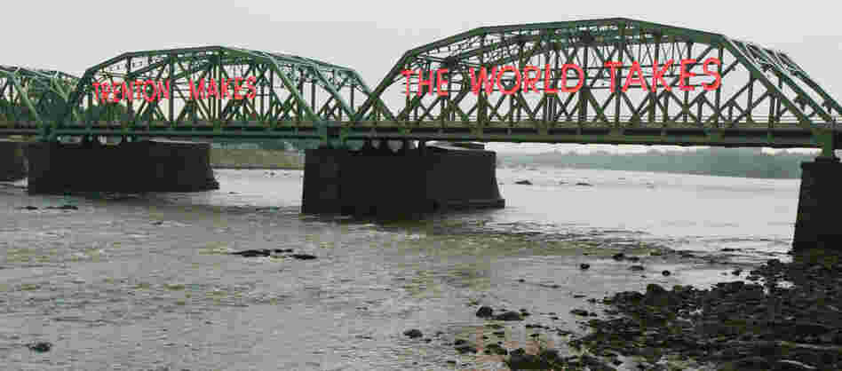 The Lower Trenton Bridge over the Delaware River reads 'Trehton Makes. The World Takes.""