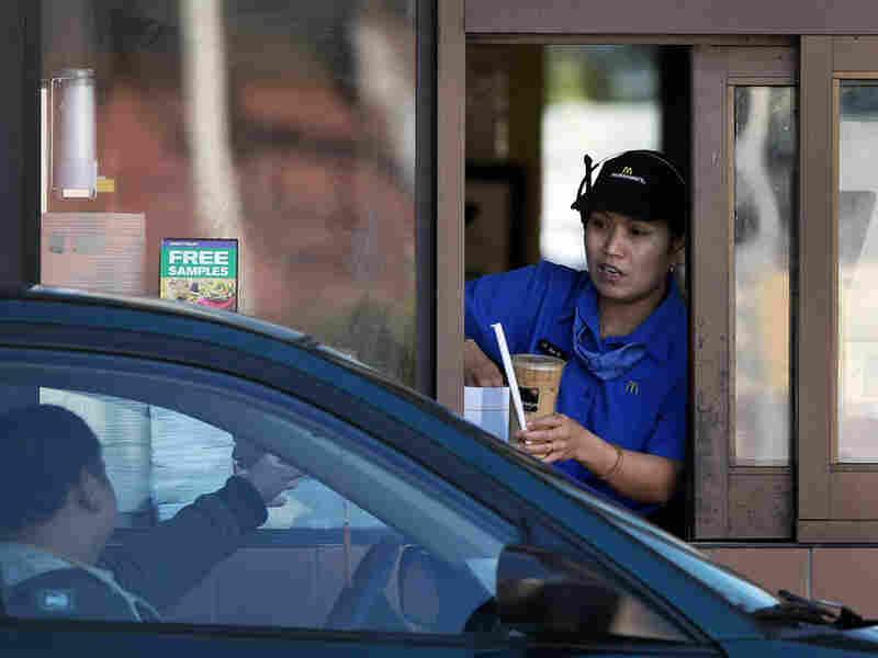 A McDonald's employee hands an order to a customer.