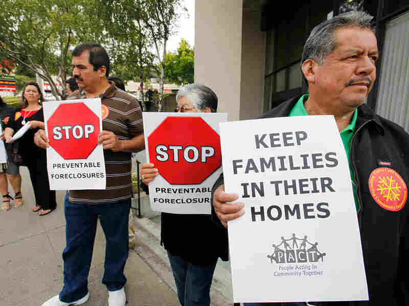 Demonstrators, whose homes are under foreclosure or lost their homes to foreclosure, holds signs.