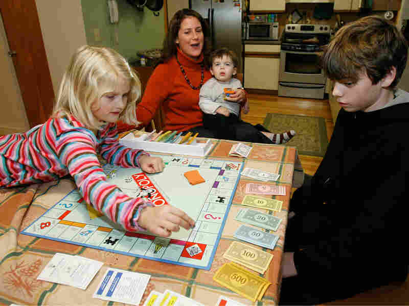A family plays Monopoly in their kitchen.