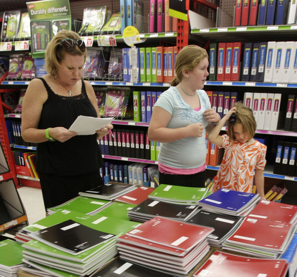 Ann Brown (left) and daughters Emily, 11, and Julie Anne, 5, shop for school supplies at a Staples store in Little Rock, Ark. Early reports from retailers show modest revenue gains in July.