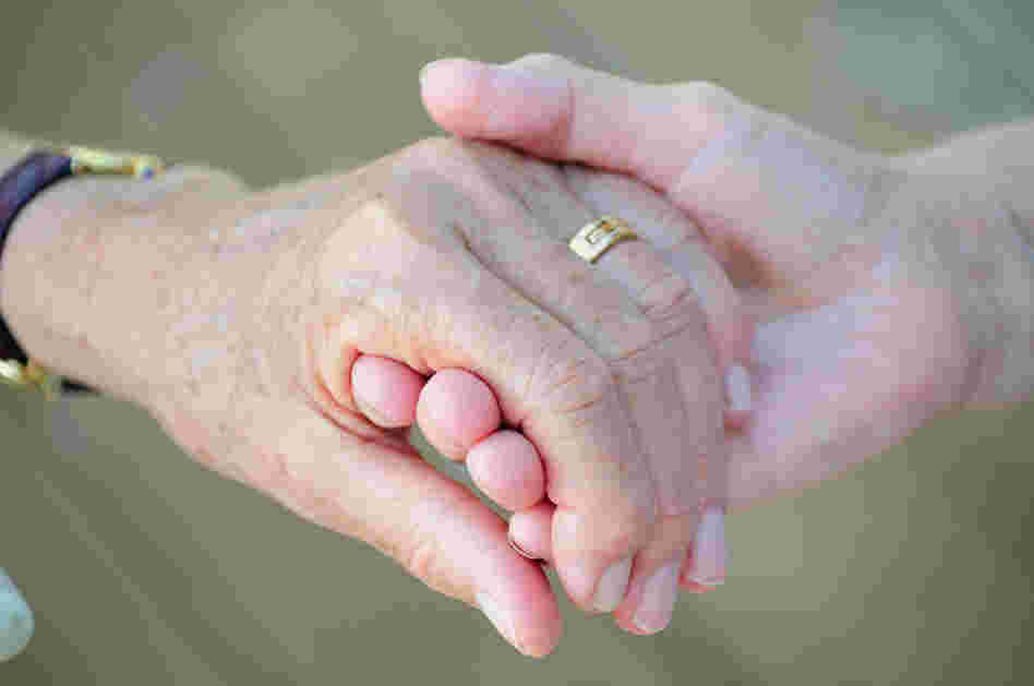 Two older women holding hands