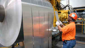 An employee inspects finished rolls of aluminum at an Alcoa facility