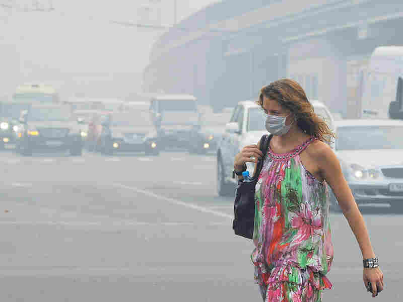 A Russian woman wears a face mask to protect herself from acrid smoke