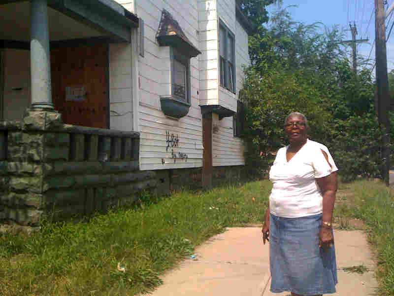 Edith Crum stands in front of a house owned by out-of-state investors that she wants torn down.
