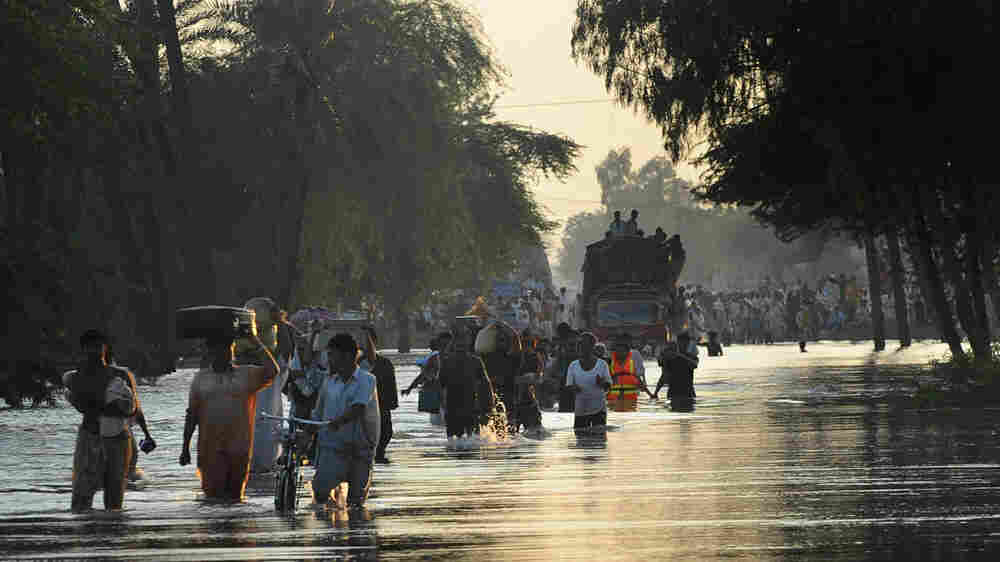 Pakistani villagers walk Tuesday in a flooded area southwest of Multan.