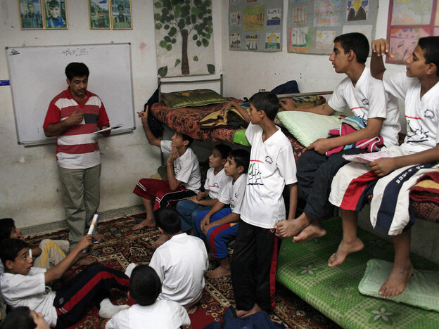 An Iraqi social worker teaches children at Beit Al-Iraq Al-Amen orphanage in Baghdad's Sadr City district in November 2007.