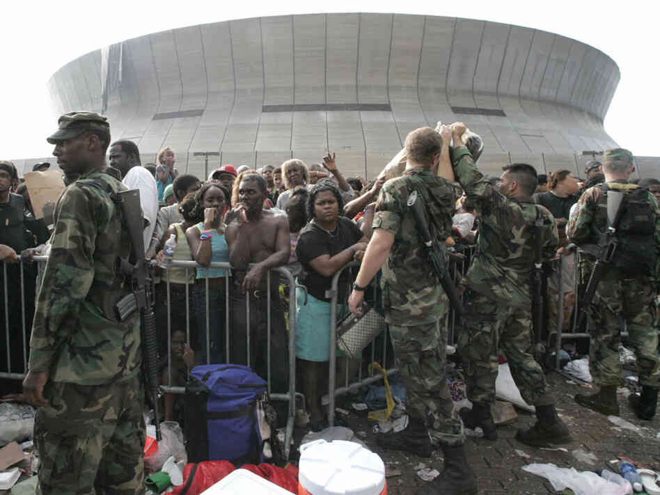 Soldiers stand guard as people wait to leave the Superdome on Sept. 1, 2005.