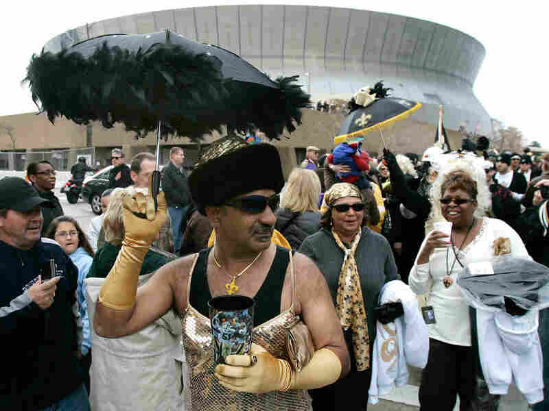 A man in a dress parades past the Superdome to celebrate the Saints' appearance in the Super Bowl.