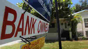 A  'Bank Owned' sign is seen in front of a foreclosed home in Miami.
