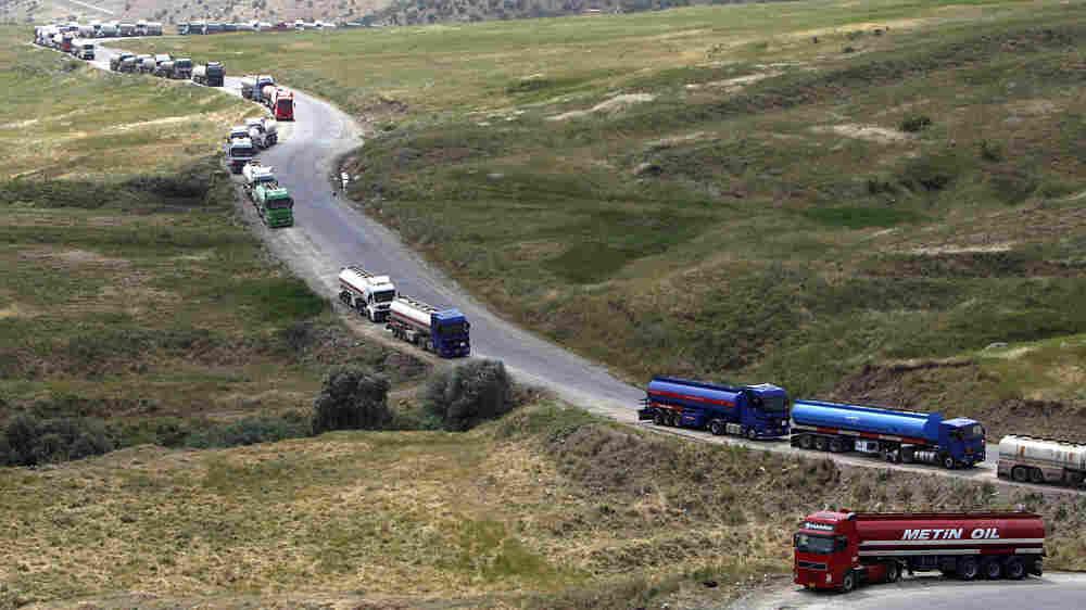 Trucks carrying oil snake their way through Haj Omran in Iraq's Kurdistan on the way to Iran