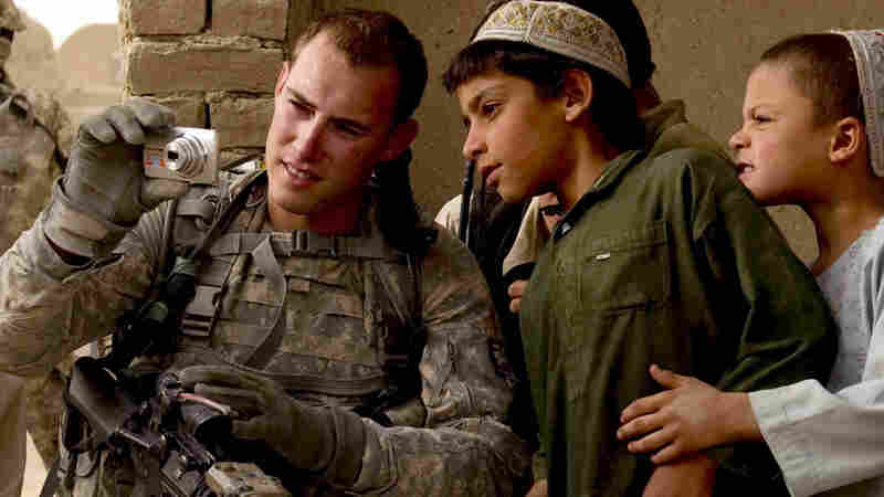 An American soldier shows pictures to Afghan boys; Kandahar province; July 28.