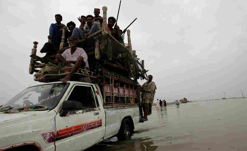 Pakistani villagers flee after heavy flooding in Jacobabad, Pakistan, on Sunday