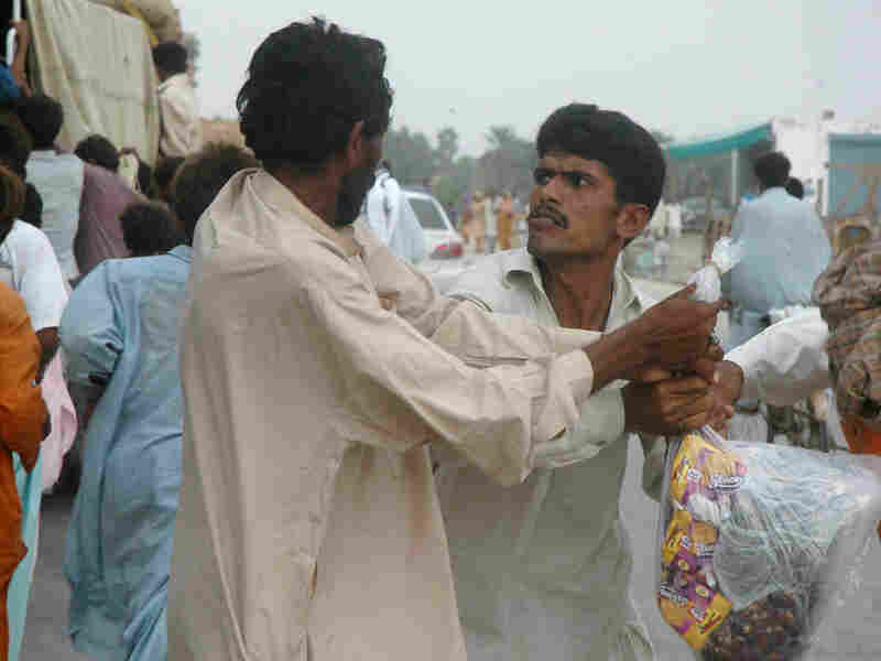 Pakistani flood victims fight for a food relief distributed by volunteers on Sunday