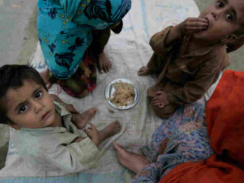 Young flood survivors share a small plate of rice at a camp in Nowshera