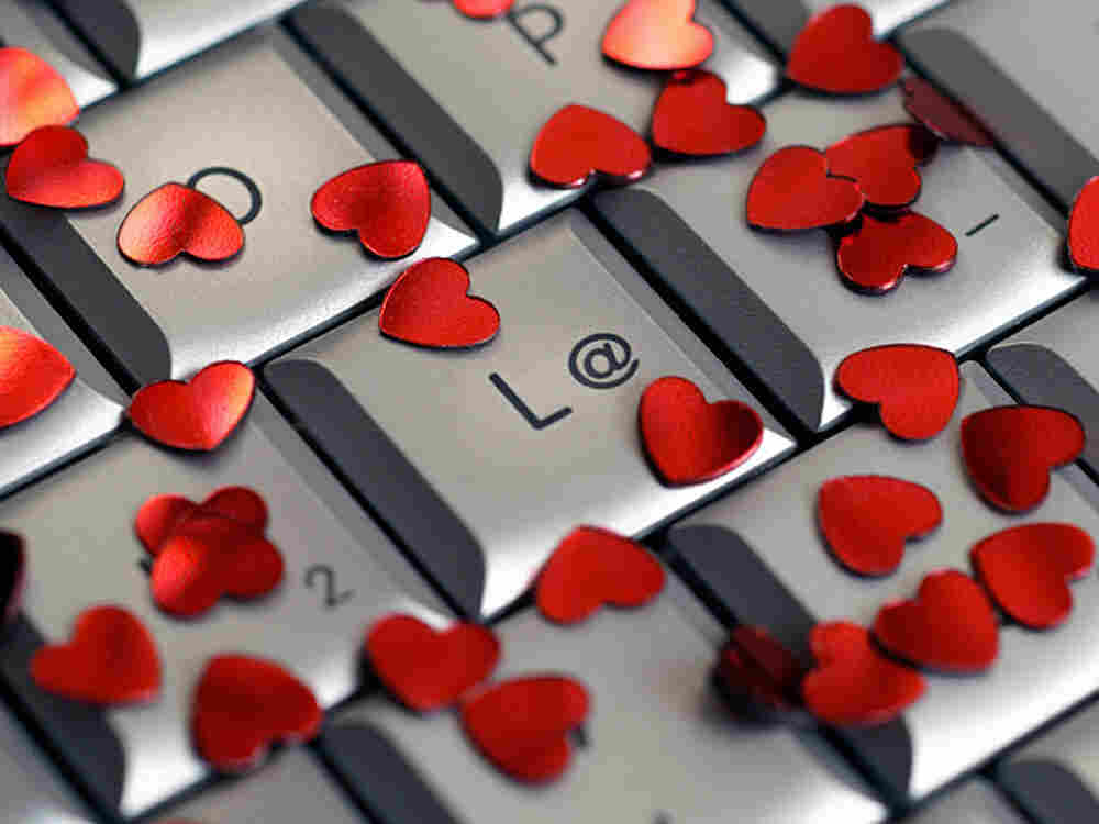 A computer keyboard covered in small red hearts.