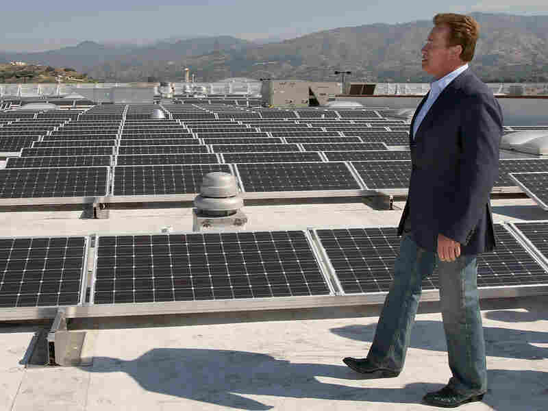 Calif. Gov. Arnold Schwarzenegger tours a solar panel installation on the roof of a Sam's Club store